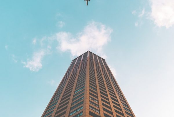 Tall modern office building with plane flying over